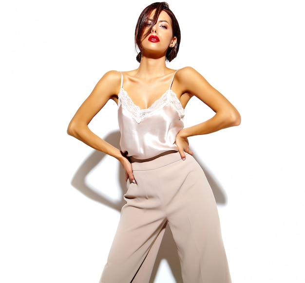 Portrait of beautiful happy cute sexy brunette woman with red lips in wide classic pants on white background