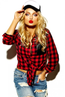 Portrait of beautiful happy cute smiling blonde woman bad girl in casual red hipster winter checkered flannel shirt and blue jeans clothes with red lips and cap