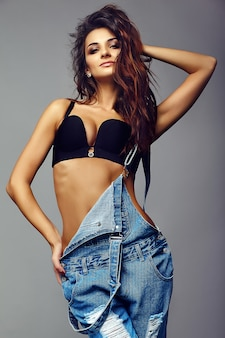 Portrait of beautiful happy cute smiling brunette woman bad girl in casual hipster denim overalls clothes in black lingerie
