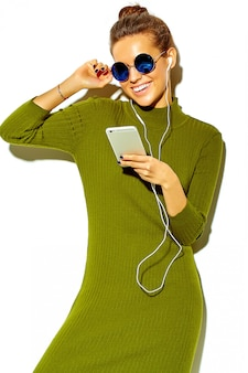 Portrait of beautiful happy cute smiling brunette woman girl in casual green hipster summer clothes  isolated on white in sunglasses listening music in smartphone with headphones
