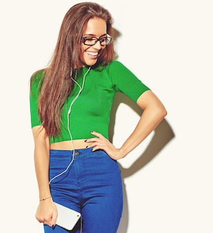 Portrait of beautiful happy cute smiling brunette woman girl in casual green hipster summer clothes with no makeup isolated on white in glasses listening music in smartphone with headphones