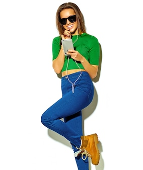 Portrait of beautiful happy cute smiling brunette woman girl in casual green hipster summer clothes with no makeup isolated on white in sunglasses listening music in smartphone with headphones