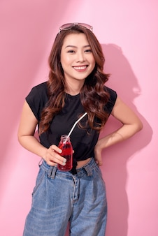 Portrait of beautiful happy cute woman girl in casual  summer clothes drink red soda water from bottle with straw over pink wall