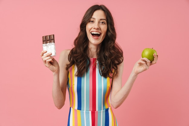 Portrait of beautiful happy emotional cute woman posing isolated over pink wall holding apple and chocolate