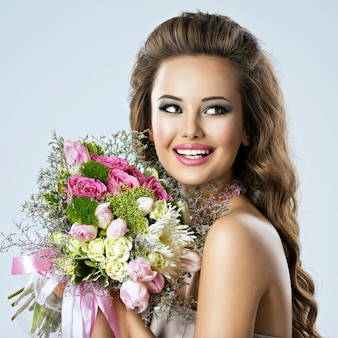 Portrait of beautiful happy girl with flowers in hands. young attractive woman holds the bouquet of spring flowers