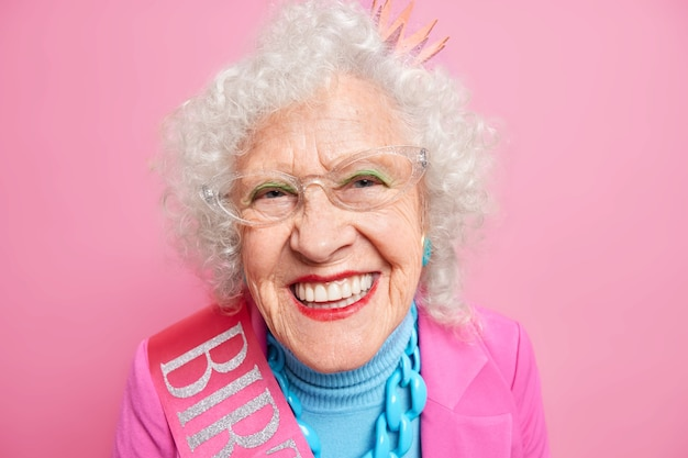 Portrait of beautiful happy grandmother smiles toothily wears red lipstick has white perfect teeth dressed in festive clothes enjoys retirement expresses positive emotions. people age beauty concept