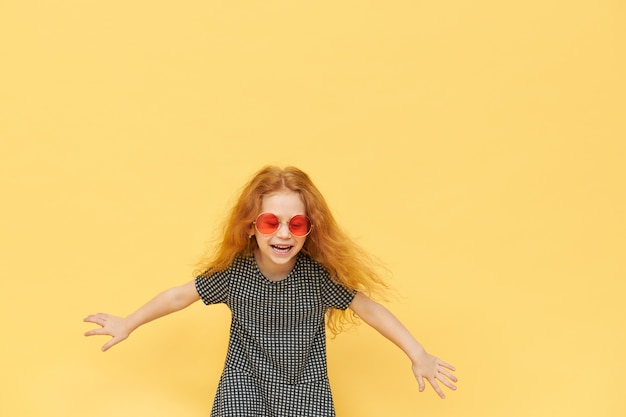 Portrait of beautiful happy little girl in trendy shades and dress keeping arms wide apart and laughing