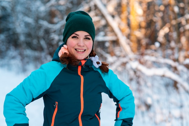 Portrait of beautiful happy positive young woman standing in a winter forest at a cold sunny day in hat