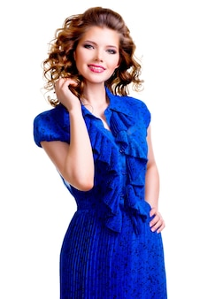 Ritratto di bella donna sorridente felice in abito blu con la mano vicino al viso - isolato su uno sfondo bianco.