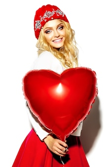 Portrait of beautiful happy sweet cute smiling blonde woman woman in casual hipster clothes, in pink skirt and winter warm beanie with red heart balloon in hands
