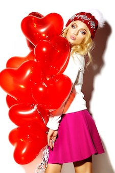 Portrait of beautiful happy sweet cute smiling blonde woman woman in casual hipster clothes, in pink skirt and winter warm beanie with red heart balloons in hands