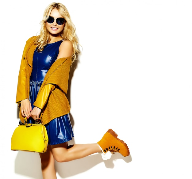 Portrait of beautiful happy sweet smiling blonde woman girl in casual hipster warm winter sweater clothes, with yellow handbag in sunglasses