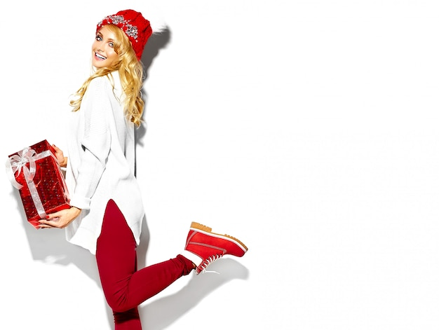 Portrait of beautiful happy sweet smiling blonde woman girl holding in her hands big christmas gift box in casual red hipster winter clothes, in white warm sweater standing on one leg