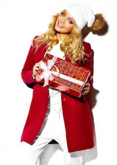 Portrait of beautiful happy sweet smiling blonde woman girl holding in her hands big christmas gift box in casual red hipster winter clothes