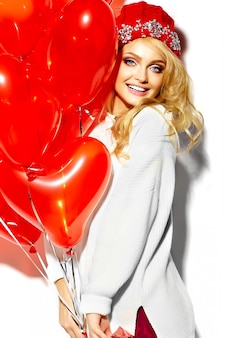 Portrait of beautiful happy sweet smiling blonde woman girl holding in her hands big christmas gift box and heart balloons in casual red hipster winter clothes, in white warm sweater