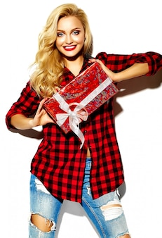 Portrait of beautiful happy sweet smiling blonde woman girl holding in her hands christmas gift box in casual red hipster winter checkered flannel shirt clothes and blue jeans