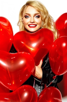 Portrait of beautiful happy sweet smiling blonde woman girl holding in her hands red heart balloons in casual black hipster clothes