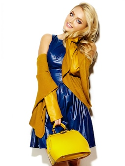 Portrait of beautiful happy sweet smiling blonde woman woman in casual hipster warm winter sweater clothes, with yellow handbag