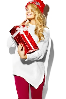 Portrait of beautiful happy sweet smiling blonde woman woman holding in her hands big christmas gift box in casual red hipster winter clothes, in white warm sweater