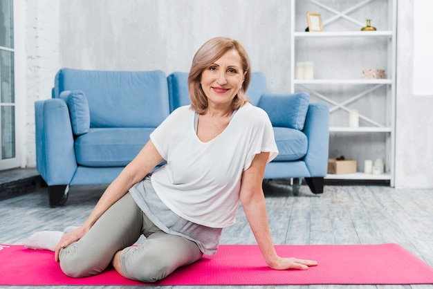 Portrait of a beautiful happy woman sitting on pink yoga mat looking at camera