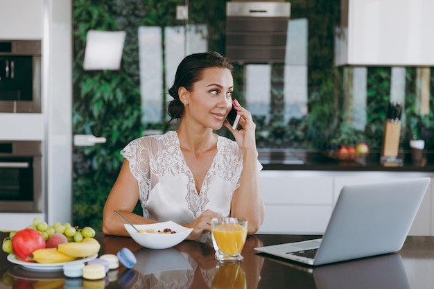 The portrait of beautiful happy woman talking on a mobile phone while breakfast with laptop on the table