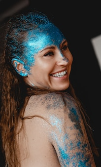 Portrait of beautiful happy woman with blue sparkles on her face. the concept of freaks and aliens. people are different from others. individuality