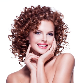 Ritratto di bella donna felice con la posa castana dei capelli ricci - isolata su bianco.