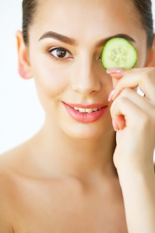 Portrait beautiful happy woman with cucumbers to eyes at home.