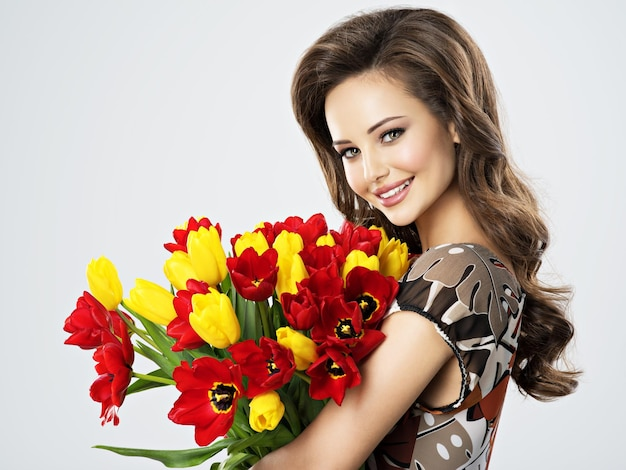 Portrait of beautiful happy woman with flowers in hands. young attractive young girl holds the bouquet of red and yellow tulips