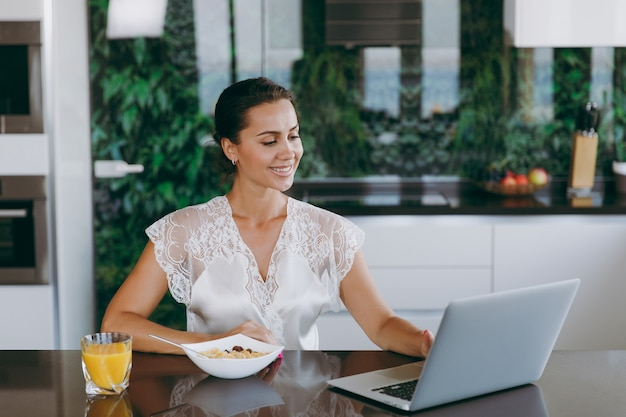 The portrait of beautiful happy woman working with laptop while breakfast with cereals and milk
