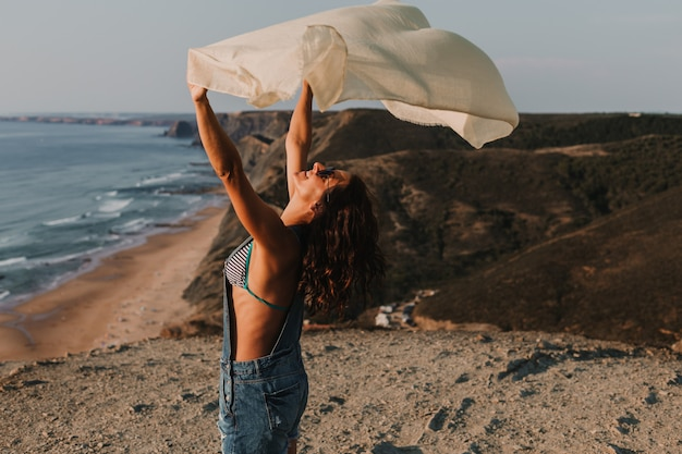 Portrait of a beautiful happy young woman playing with a handkerchief and the wind on the top of a hill. summer time. lifestyle