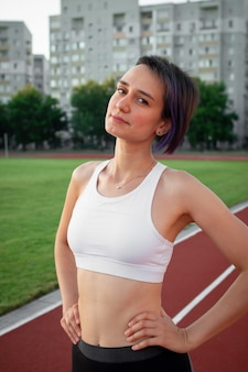 Portrait beautiful happy young woman runner athlete in white t-shirt and sportswear at the stadium looking at the camera and smiling in the early morning run and workout at the outdoor stadium