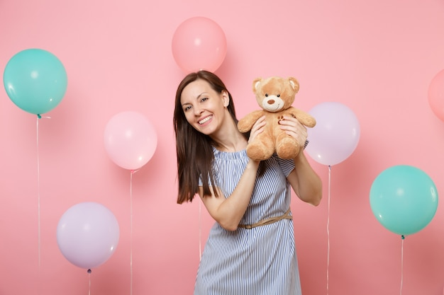 Portrait of beautiful happy young woman wearing blue dress holding teddy bear plush toy on pastel pink background with colorful air balloons. birthday holiday party, people sincere emotions concept.