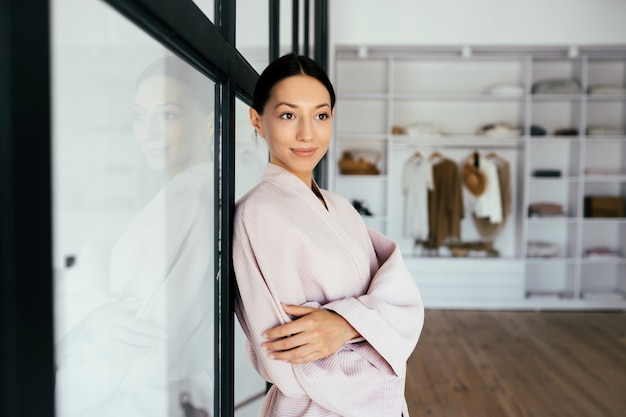 Portrait of a beautiful healthy woman in bathrobe posing at camera indoors