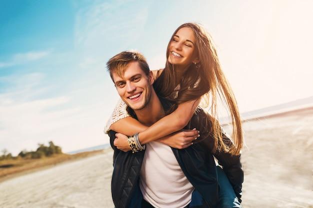 美しい健康な若い大人のガールフレンドとボーイフレンドの幸せを抱いての肖像画。ビーチ沿いの日当たりの良い春に恋に若いきれいなカップル。暖かい色。