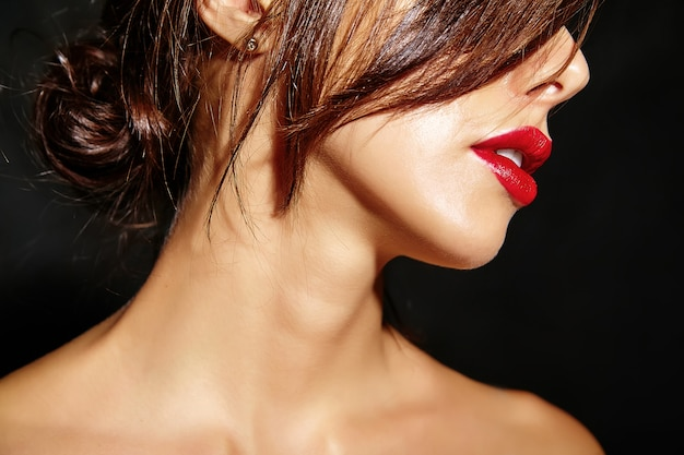 Portrait of beautiful hot cute sexy brunette woman with red lips on black background