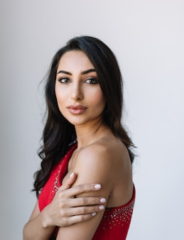 Portrait of beautiful indian woman wearing trendy red dress, looking at camera. stylish asian fashion model posing for pictures