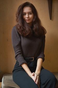 Portrait of beautiful intelligent brunette in loft cafe. charming thoughtful woman