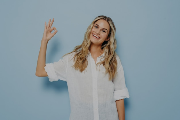 Portrait of beautiful joyful blonde woman making on camera ok gesture or okay sign with fingers, female smiling happily and showing perfect white teeth. body language concept