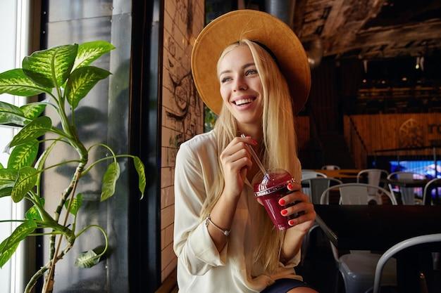 Ritratto di bella gioiosa donna bionda dai capelli lunghi incontrare gli amici nella moderna caffetteria ed essere di buon umore, tenendo la tazza di frullato in mano e guardando fuori dalla finestra con un ampio sorriso felice