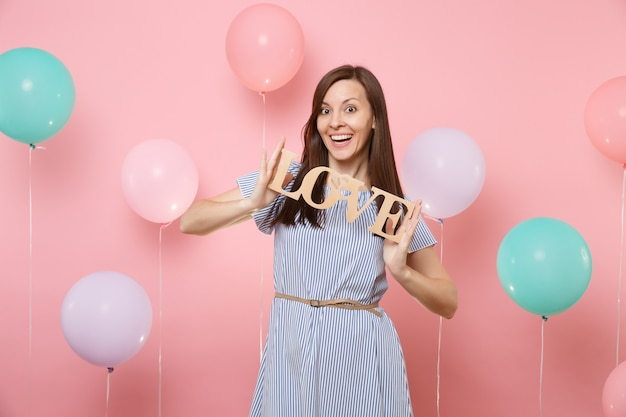 Portrait of beautiful joyful young woman in blue dress holding wooden word letters love on pastel pink background with colorful air balloons. birthday holiday party, people sincere emotions concept.