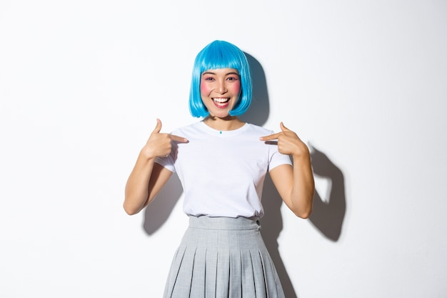 Portrait of beautiful korean girl in blue wig pointing at herself with cheerful smile, standing in halloween costume.