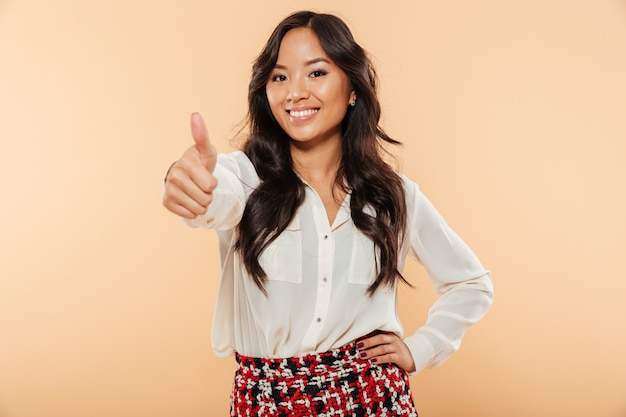 Portrait of beautiful lady in casual wear showing thumb up on camera expressing good choice being isolated over peach background