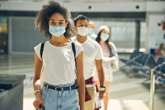 Portrait of beautiful lady in protective mask and denim skirt waiting for a flight by plane