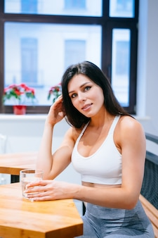 Portrait of beautiful lady in sporty top with glass of water