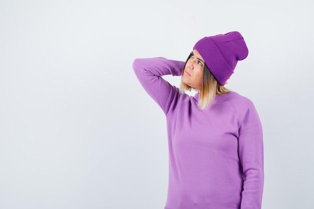 Ritratto di bella signora con la mano sul collo in maglione, berretto e guardando la vista frontale premurosa