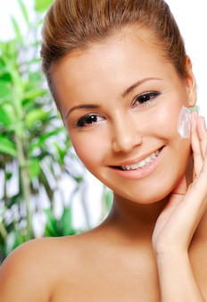 Portrait of beautiful latinos woman applying moisturiser cream