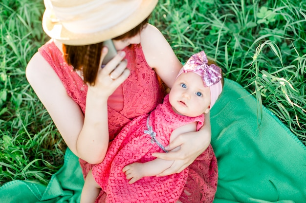 Portrait of a beautiful, laughing girl with gorgeous blue eyes being held by her mother, on her back, in her lap in the garden