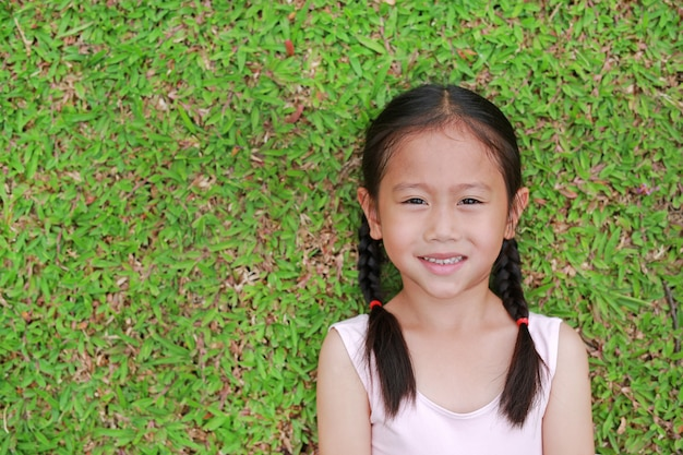 Portrait of beautiful little asian child girl with two ponytail hair lying on green grass lawn.