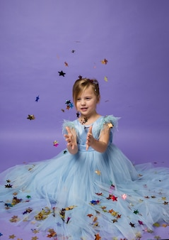 Portrait of a beautiful little girl in a blue princess dress sitting on the floor and catching colorful confetti stars on purple